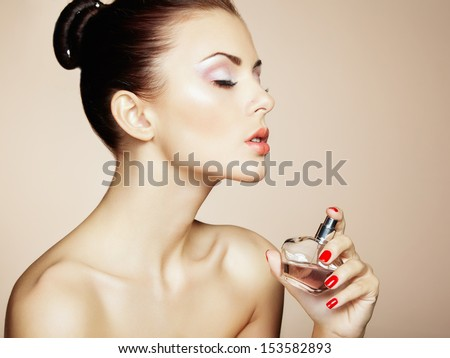 Young beautiful woman with bottle of perfume. Perfect Makeup. Fashion photo - stock photo