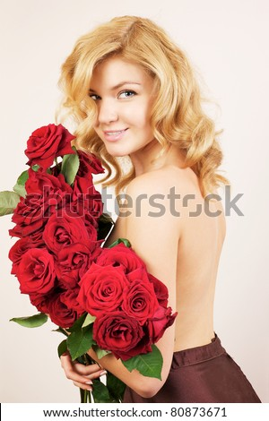 Young beautiful woman with  bunch of red roses - stock photo