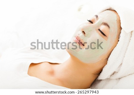 Young beautiful woman with clay facial mask - stock photo