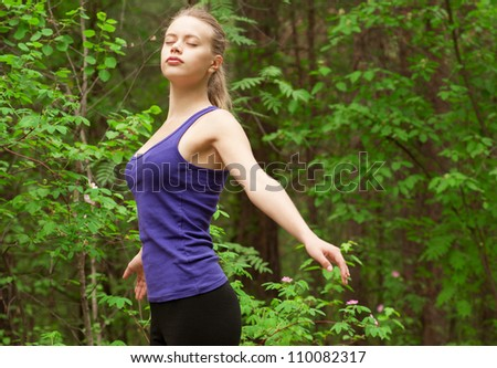 Young beautiful woman with closed eyes doing yoga meditation in forest outdoors - stock photo