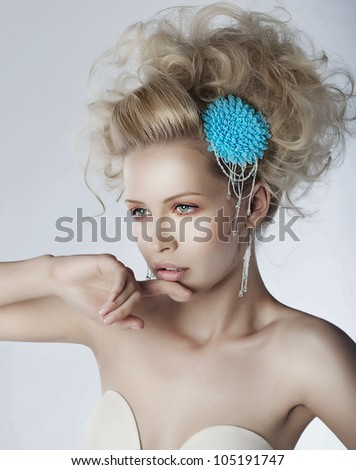 Young beautiful woman with creative elegant hairstyle and brooch. Sexy blonde model with long curly hair - stock photo