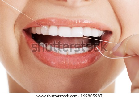 Young beautiful woman with dental floss. Over white background. - stock photo