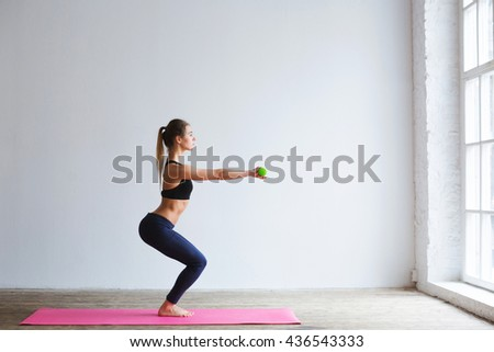 Young beautiful woman with engaged in a perfect figure exercises with dumbbells in the gym. - stock photo