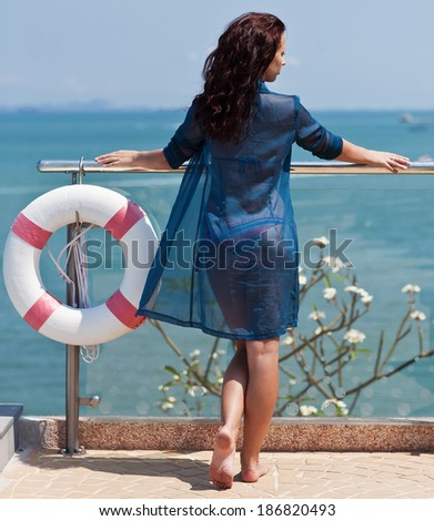 Young beautiful woman with floating equipment enjoying the ocean view - stock photo