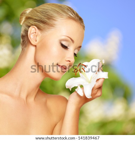 Young beautiful woman with flower at face - stock photo