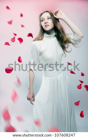 Young beautiful woman with flying red petals of roses - stock photo