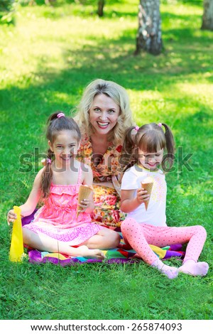 Young beautiful woman with girls kids daughters sitting on grass, smiling eating ice cream - stock photo