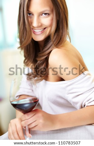 Young beautiful woman with glass of red wine looking at camera - stock photo