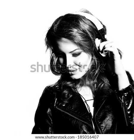 Young beautiful woman with headphones listening music. Teenager girl and music concept. Black and white. - stock photo