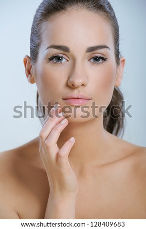 Young beautiful woman with health skin touching her skin around the mouth - stock photo
