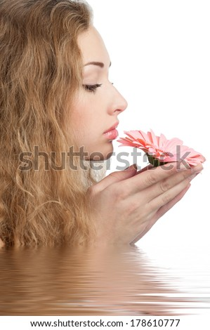 Young beautiful woman with healthy skin and pink flower in her hand in water. Beauty treatment concept  - stock photo