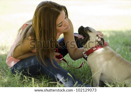 Young beautiful woman with her pug dog at the park - stock photo