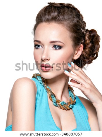 Young beautiful woman with jewelry. Girl Fashion  in blue dress wearing bijouterie. Attractive model with blue nails. Pretty model posing over white background - stock photo