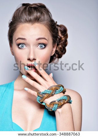 Young beautiful woman with jewelry. Girl Fashion  in blue dress wearing bijouterie. Attractive model with blue nails.  - stock photo