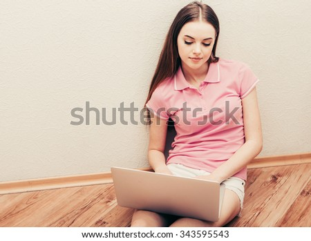 Young beautiful woman with laptop notebook on floor home surfing internet  - stock photo