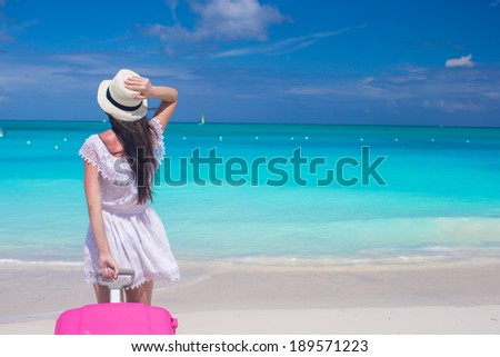Young beautiful woman with large suitcase on tropical beach - stock photo