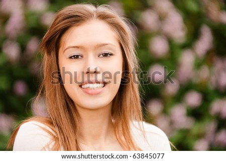 Young beautiful woman with long hair smiles against blossoming bush in city spring park. - stock photo