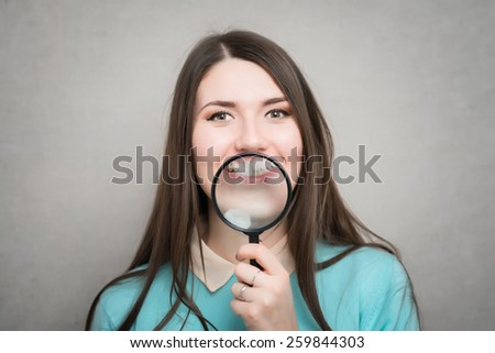 Young beautiful woman with magnifying glass. - stock photo