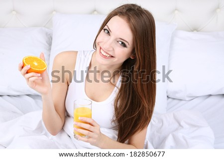 Young beautiful woman with orange juice in bed close-up - stock photo