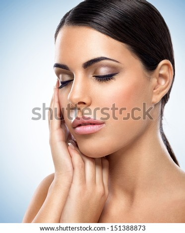 Young beautiful woman with perfect skin posing with closed eyes - stock photo