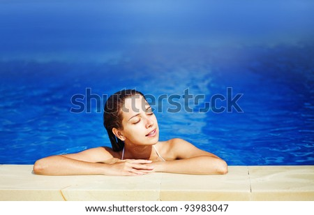 Young beautiful woman with pleasure in swimming pool in sunny day - stock photo