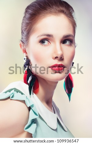 Young beautiful woman with red glamour lips and eye arrow make-up wearing fancy plastic earrings, on colored background, retro styled beauty - stock photo