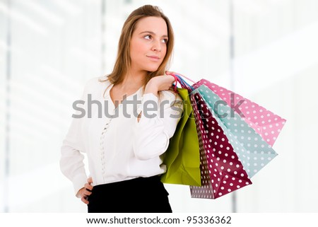 Young beautiful woman with shopping bags on the background of shop windows - stock photo