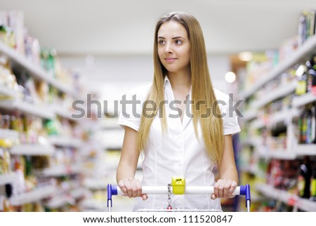 Young beautiful woman with shopping cart - stock photo