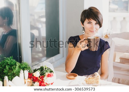 Young beautiful woman with short hair drinking steaming coffee in a street cafe - stock photo