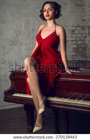 young beautiful woman with shortcutted hair and red lips sits on the piano - stock photo