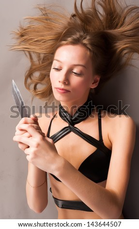 Young beautiful woman with steel knife at grey background - stock photo