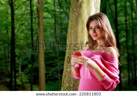 Young beautiful woman with toothy smile send a text message vie mobile phone - stock photo