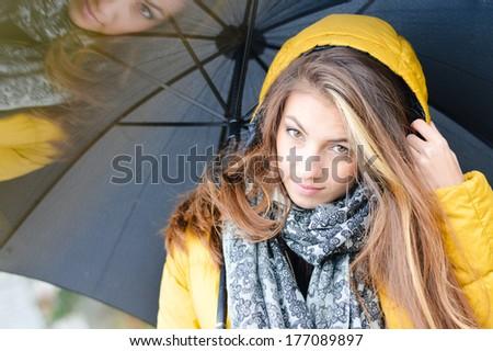 Young beautiful woman with umbrella wearing warm yellow coat - stock photo