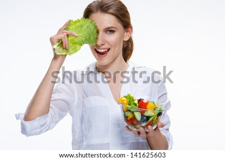 Young beautiful woman with vegetable salad / comic girl of the european appearance closes an eye with cabbage leaf and holds vegetable salad in transparent crockery - isolated on white background  - stock photo