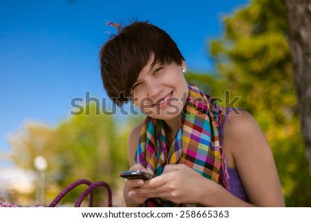 Young beautiful woman writes an SMS to your mobile phone - stock photo