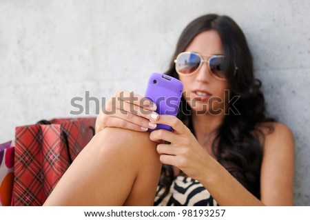 Young beautiful woman writing a sms message on phone - stock photo