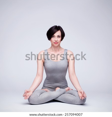 young beautiful woman yoga posing on a gray studio background - stock photo