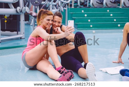 Young beautiful women friends taking a selfie with smartphone sitting on the floor of a fitness center after hard training day - stock photo