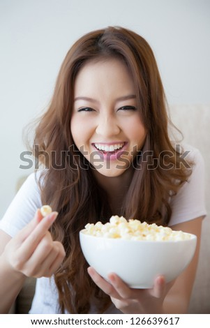 Young beautiful women holding a bowl of popcorn - stock photo