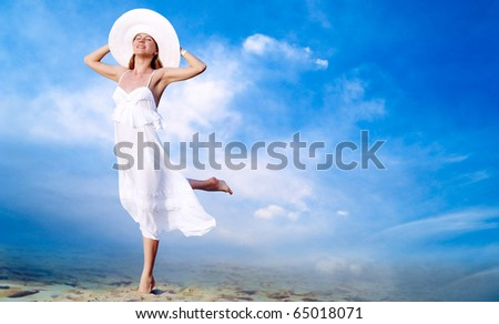 Young beautiful women in the white with pareo on the blue sky background - stock photo