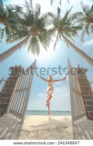 Young beautiful women jumping on the sunny tropical  - stock photo