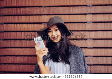 Young beautiful women lady touching and browsing her smart-phone on a wooden background - stock photo