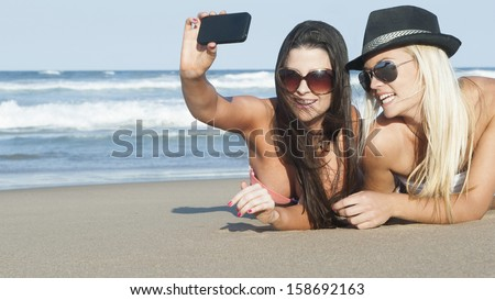 Young beautiful women on beach taking photo with smart phone camera - stock photo