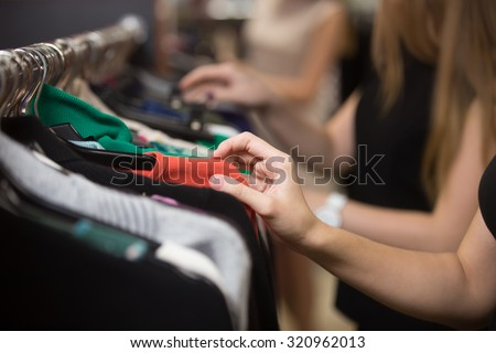 Young beautiful women shopping in fashion mall, choosing new clothes, looking through hangers with different casual colorful garments on hangers, close up of hands - stock photo