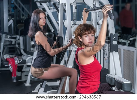 Young beautiful women training in fitness center - stock photo