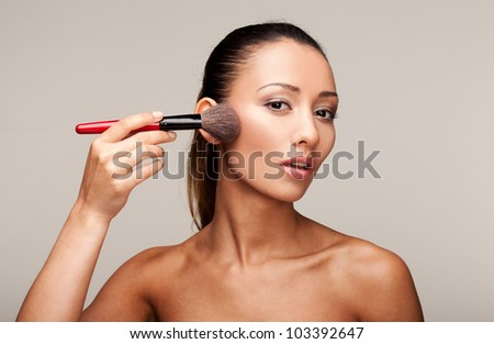 Young beautiful womman applying makeup using a brush - stock photo