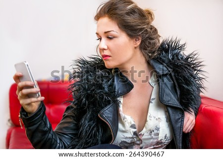 Young beautiful young lady touching and browsing her smart phone at home. - stock photo