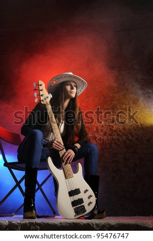 Young beautiful young singer is sitting on stage with a bass guitar - stock photo