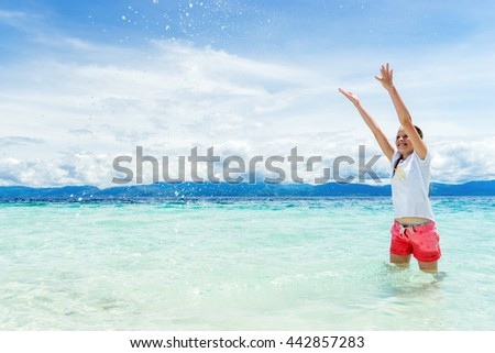 young beautifull girl playing with turquoise water at tropical island under blue sky - stock photo