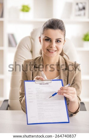 Young beauty businesswoman showing on resume in office. - stock photo